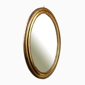 Espejo de finales del siglo XX con marco ovalado dorado