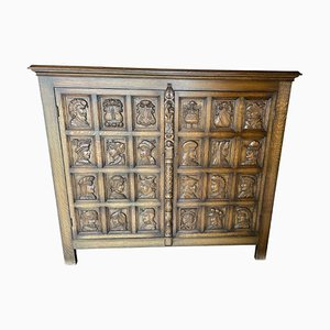 Antique Cabinet with Carved Coats of Arms and Heads on the Front