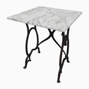 Mesa de jardín con estructura de hierro fundido y tablero de mármol