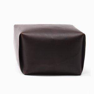 Poggiapiedi Bao in pelle scura di Viola Tonucci per Tonucci Manifestodesign