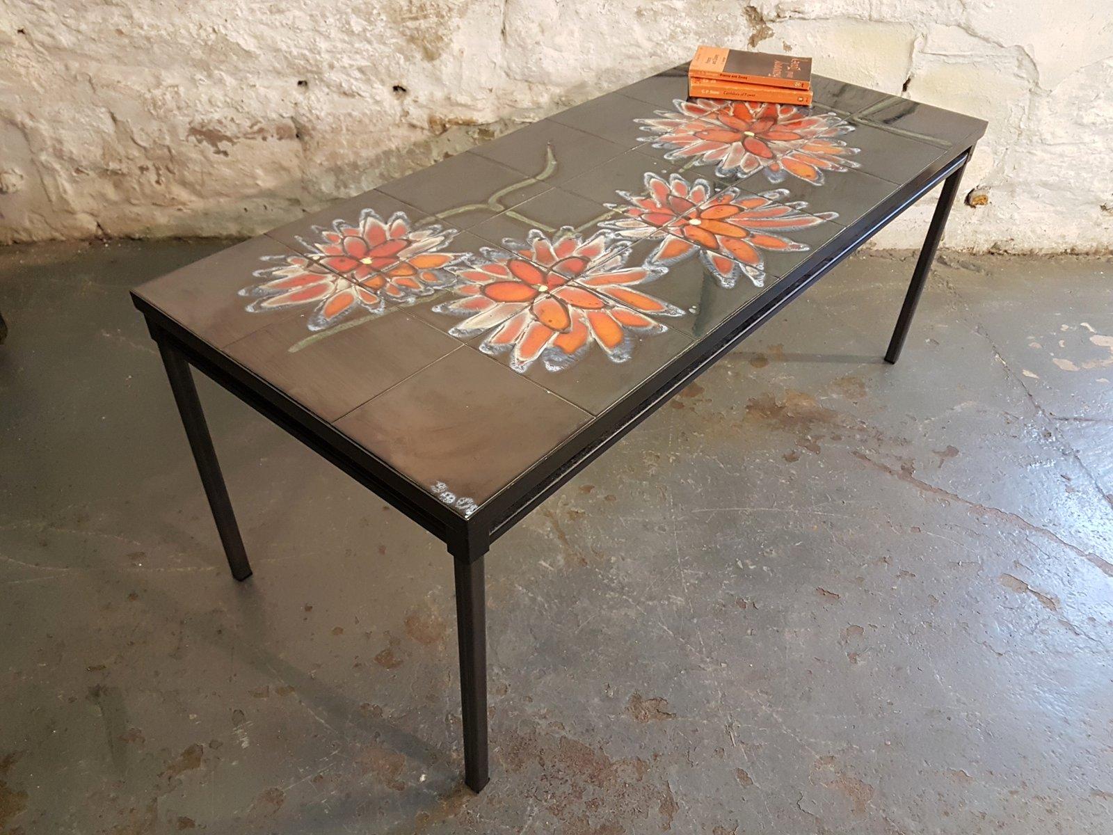 Tavolo con piastrelle nere e fiori arancioni di adri anni in